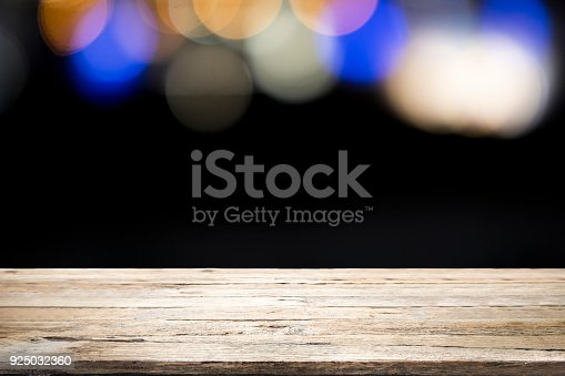 841276202istockphoto Empty wooden table platform on bokeh at nigh. 925032360