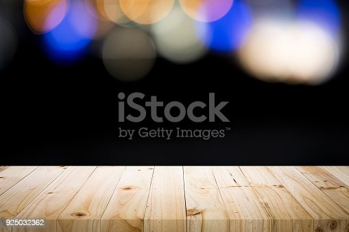 841276202istockphoto Empty wooden table platform on bokeh at nigh. 925032362