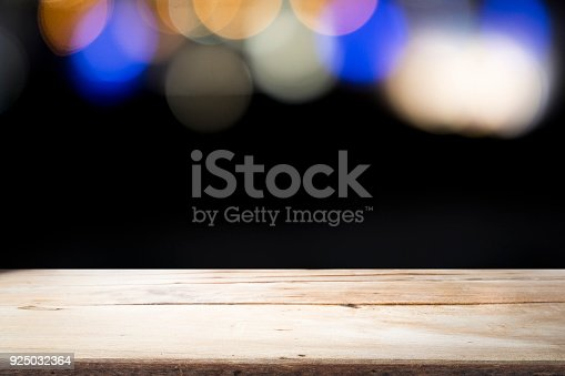 841276202istockphoto Empty wooden table platform on bokeh at nigh. 925032364
