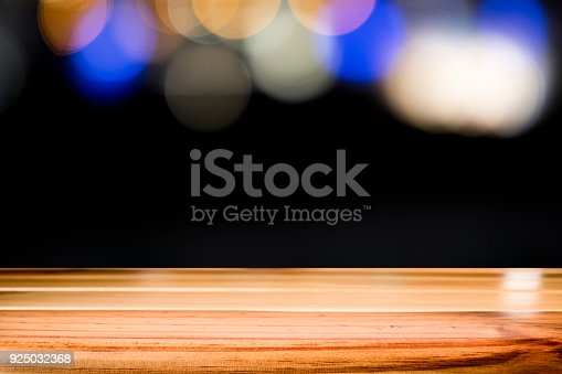 841276202istockphoto Empty wooden table platform on bokeh at nigh. 925032368