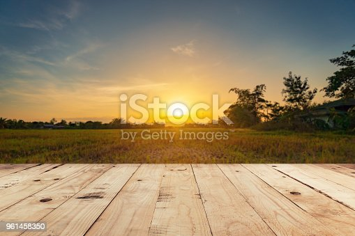 Empty wooden table top and display montage with blur background field sunset.