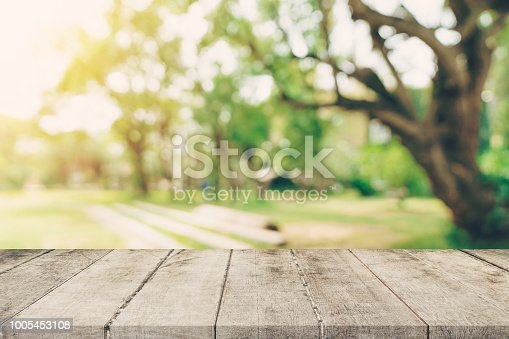 885452818istockphoto Empty wooden table top and green bokeh display montage for product with space. 1005453108