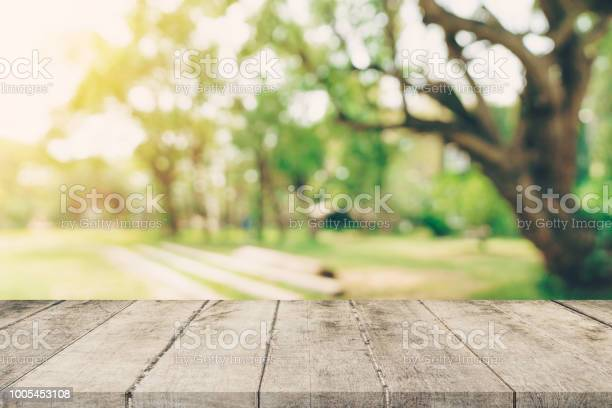 Photo of Empty wooden table top and green bokeh display montage for product with space.