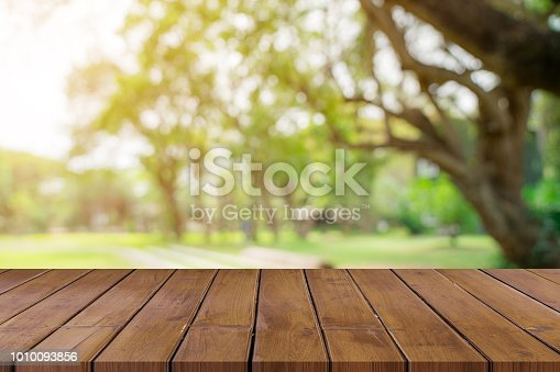 641254964 istock photo Empty wooden table top and green bokeh display montage for product with space. 1010093856