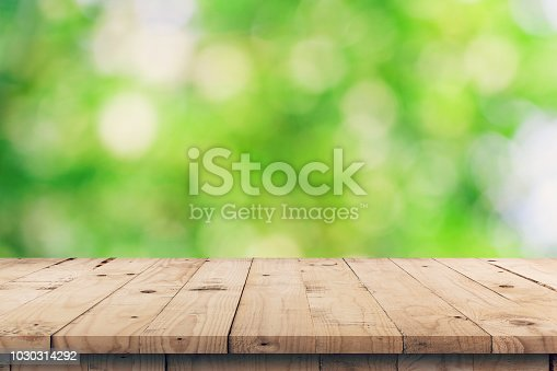 885452818istockphoto Empty wooden table top and green bokeh display montage for product with space. 1030314292