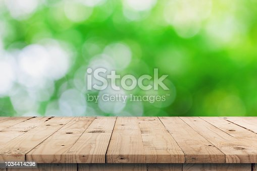 641254964 istock photo Empty wooden table top and green bokeh display montage for product with space. 1034414298
