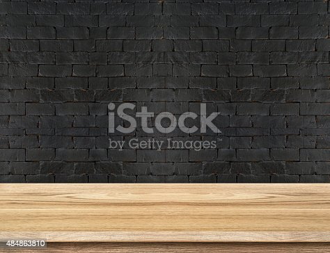 593305530istockphoto Empty Wooden Table top at black brick wall 484863810