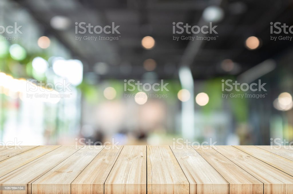 Empty wooden table top with blur coffee shop or restaurant interior...