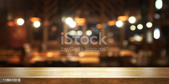 istock Empty wooden table top with blur coffee shop or restaurant interior background, 1139412018