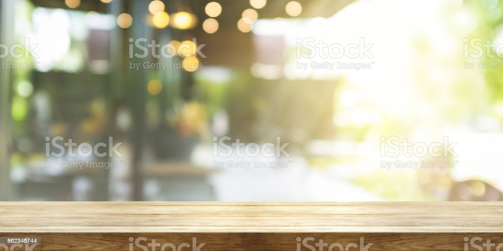 Empty wooden table top with blur coffee shop or restaurant interior background, Panoramic banner. Abstract background can be used product display. stock photo