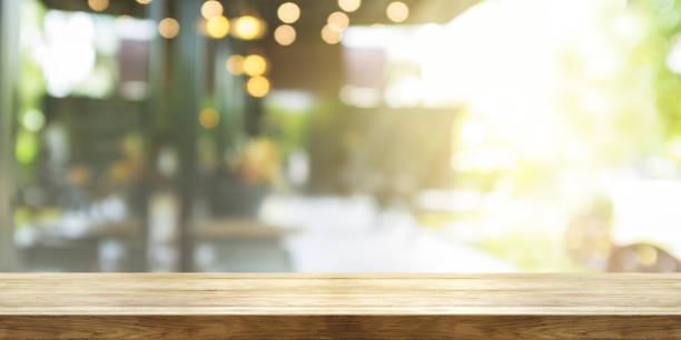 lege houten tafelblad met vervagen koffiewinkel of restaurant interieur achtergrond, panoramische banner. abstracte achtergrond kan worden gebruikt product weergeven. - restaurant table stockfoto's en -beelden