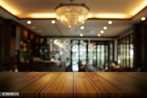 istock Empty wooden table top with blur coffee shop or restaurant interior background. Abstract background can be used product display. 878508270