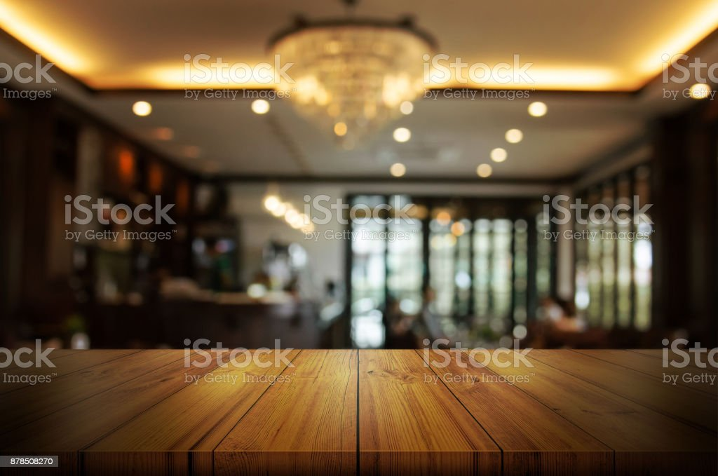 Empty wooden table top with blur coffee shop or restaurant interior background. Abstract background can be used product display. stock photo