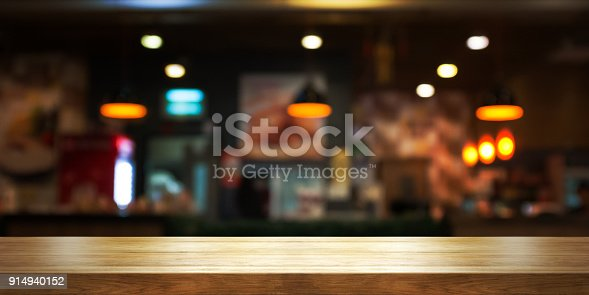 istock Empty wooden table top with blur coffee shop or restaurant interior background, Panoramic banner. 914940152