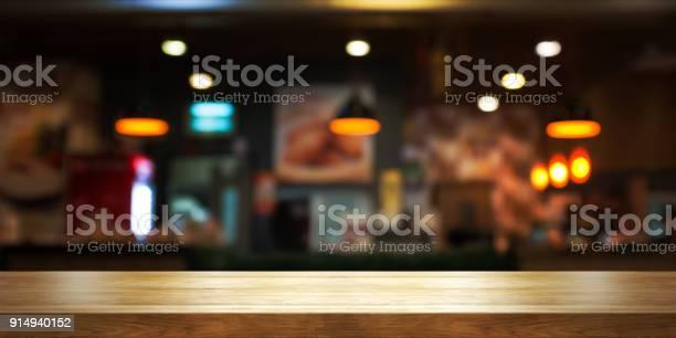 Empty wooden table top with blur coffee shop or restaurant interior picture id914940152?b=1&k=6&m=914940152&s=612x612&h=ev aynbl9ih8ypnujhmibohsvgwscydjm1a ude0rey=