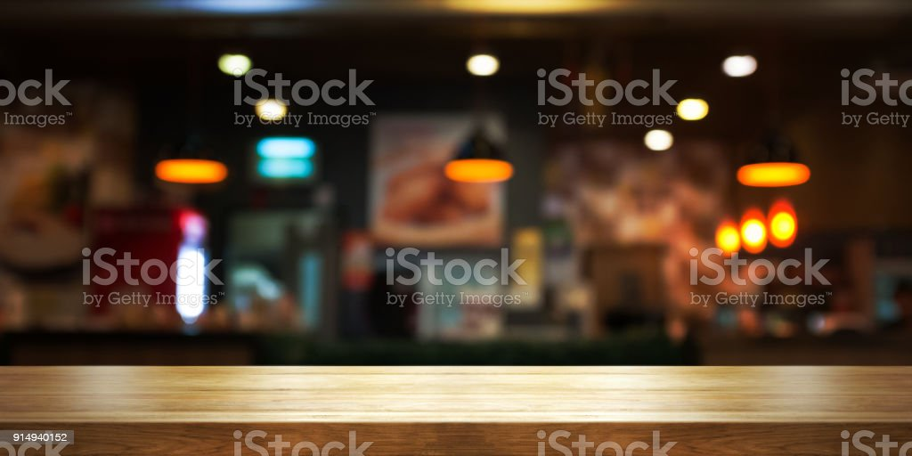 Empty wooden table top with blur coffee shop or restaurant interior background, Panoramic banner. - foto stock