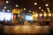 空の木製テーブル トップぼかしのコーヒー ショップやレストランのインテリア背景付き。