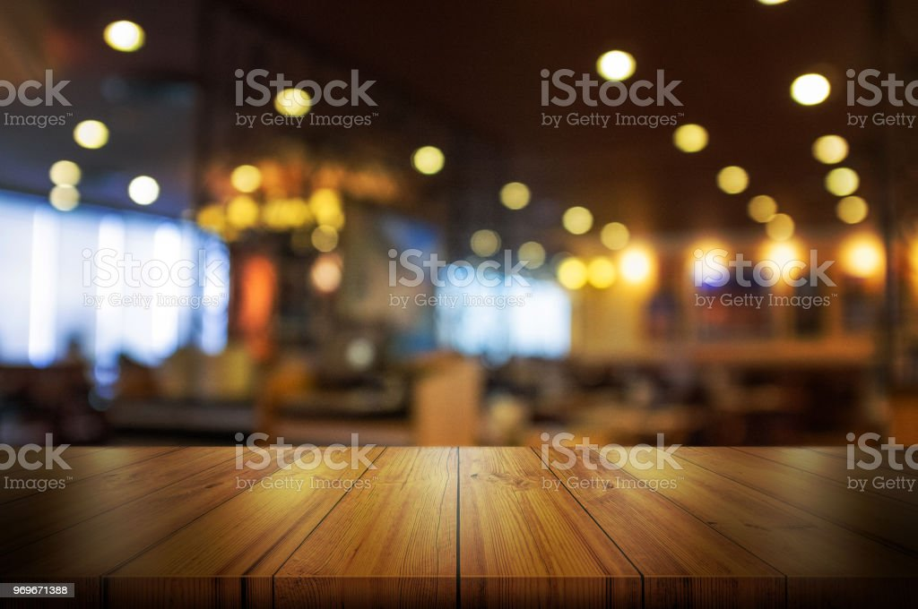 Empty wooden table top with blur coffee shop or restaurant interior background. stock photo