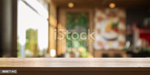 istock Empty wooden table top with blur coffee shop or restaurant interior background, Panoramic banner. 969671442