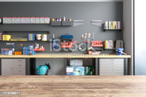 istock Empty Wooden Table Top With Blur Garage Interior 1219766511