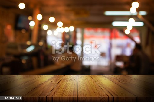 862429776 istock photo Empty wooden table top with blurred coffee shop or restaurant interior background. 1137901391