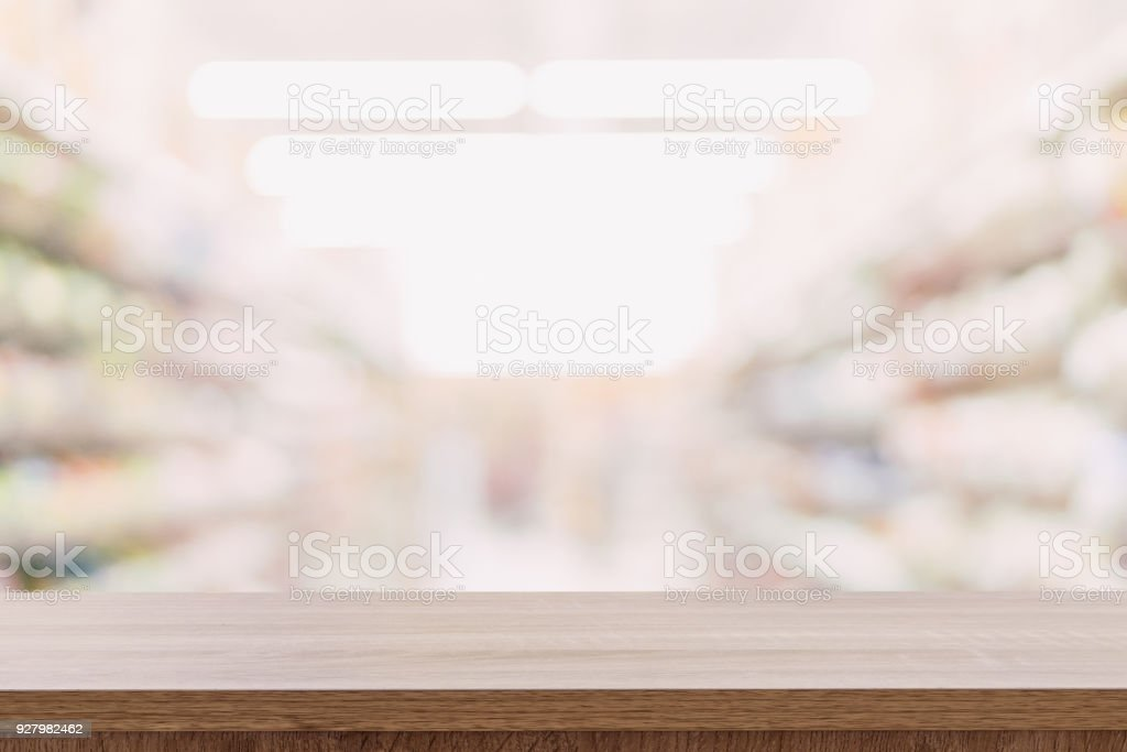 Empty wooden table top with blurred modern shopping mall background...
