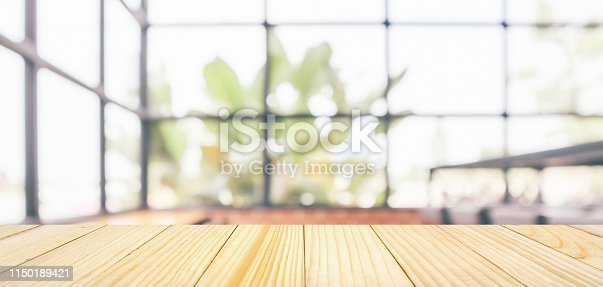istock Empty wooden table top with cafe restaurant coffee shop window interior abstract blur defocused with bokeh light background for montage product display 1150189421