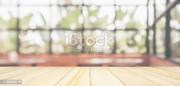istock Empty wooden table top with cafe restaurant coffee shop window interior abstract blur defocused with bokeh light background for montage product display 1150609116