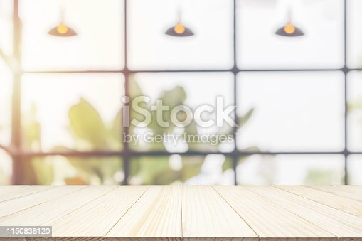 istock Empty wooden table top with cafe restaurant coffee shop window interior abstract blur defocused with bokeh light background for montage product display 1150836120