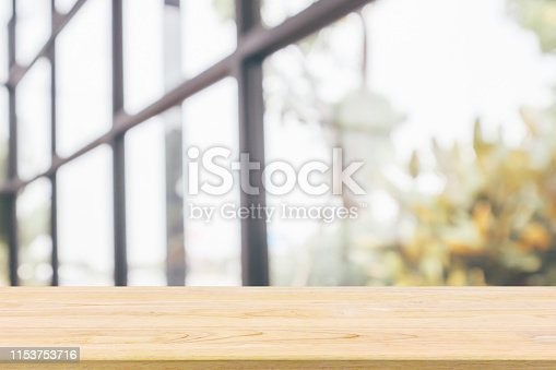 istock Empty wooden table top with cafe restaurant coffee shop window interior abstract blur defocused with bokeh light background for montage product display 1153753716