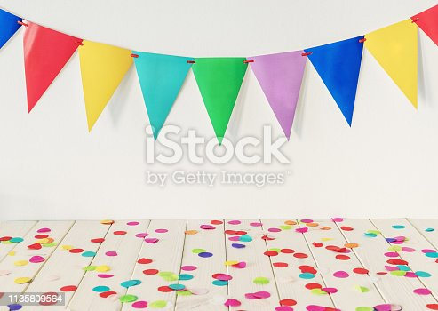 Empty wooden table top with colourful confetti and bunting