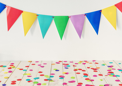 istock Empty wooden table top with colourful confetti and bunting 1135809564