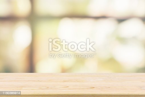 Empty wooden table top with green garden at cafe restaurant or coffee shop window abstract blur defocused with bokeh light background for montage product display