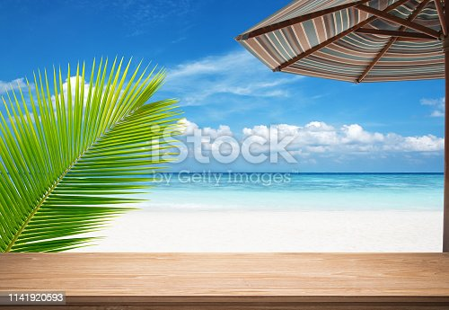677933036 istock photo Empty wooden table under beach umbrella at the seaside 1141920593