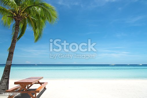 677933036 istock photo Empty wooden table under palm tree on tropical paradise beach 1139622231