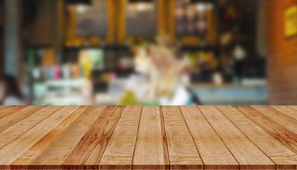 Empty wooden table with abstract blurred background of coffee shop