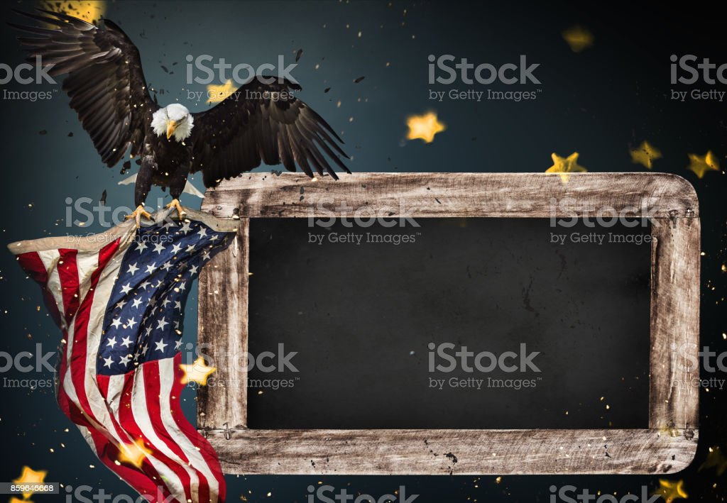 Empty wooden table with bald eagle and USA flag background stock photo