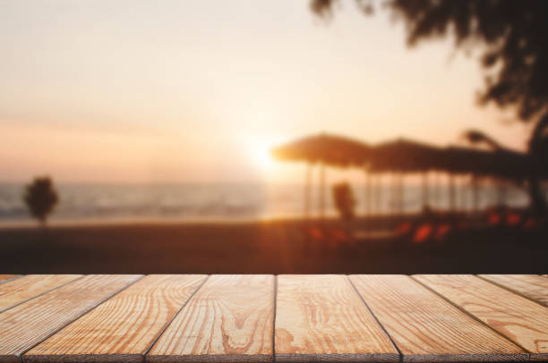empty wooden table with blurred beach and sunset background stock photo