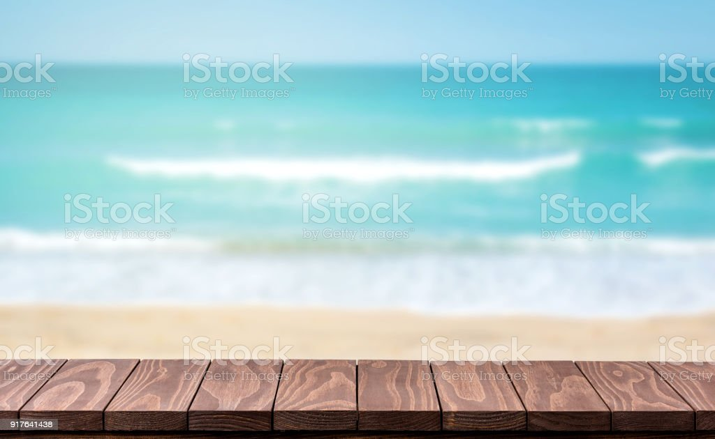 Empty wooden table with blurred beach background stock photo