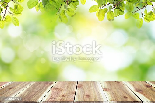 641254964 istock photo Empty wooden table with blurred city park on background The top has a natural  bokeh light,Mock up for display.  montage of product,Banner or header for advertise on social media,Spring and Summer. 1053802974