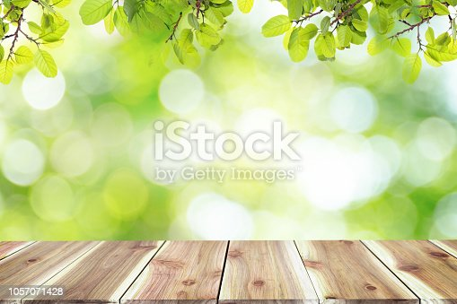 641254964 istock photo Empty wooden table with blurred city park on background The top has a natural  bokeh light,Mock up for display.  montage of product,Banner or header for advertise on social media,Spring and Summer. 1057071428