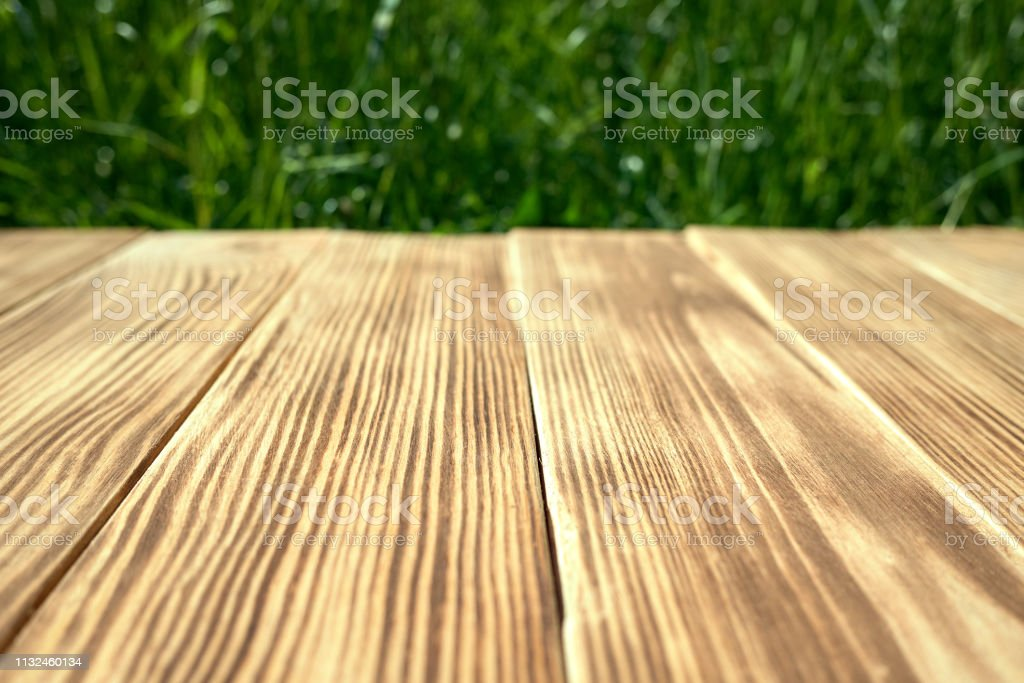 Empty wooden table with blurred green grass on background. concept...