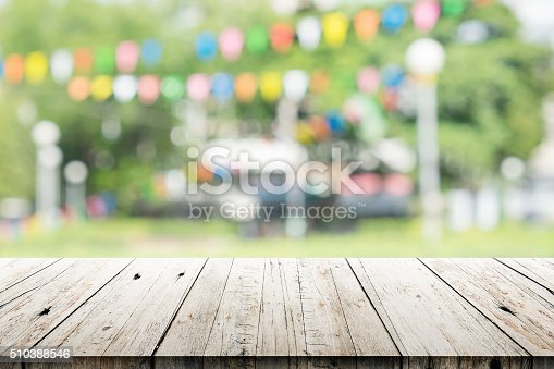 istock Empty wooden table with blurred party on background 510388546