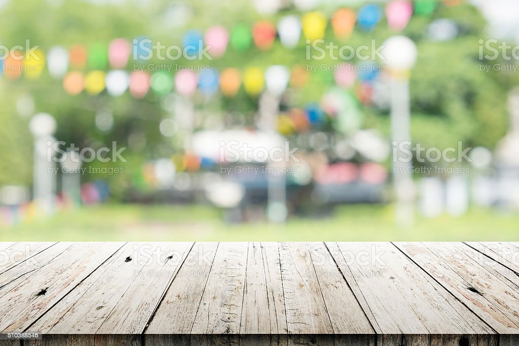 Empty wooden table with blurred party on background stock photo