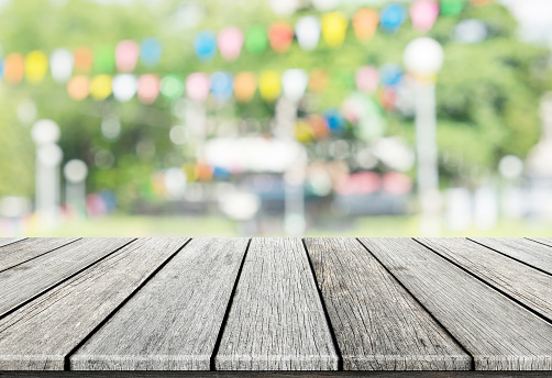 istock Empty wooden table with blurred party on background 520774956