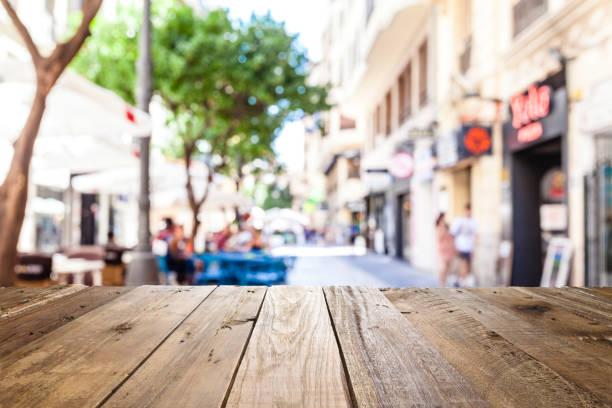 Leere Holztisch mit defokussierten Straßencafé im Hintergrund – Foto