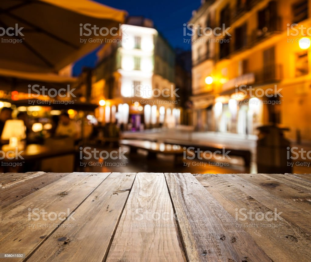 Empty wooden table with defocused street café at background stock photo
