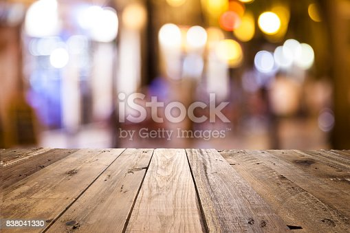 istock Empty wooden table with defocused street lights at background 838041330