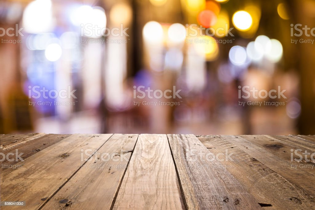 Empty wooden table with defocused street lights at background stock photo