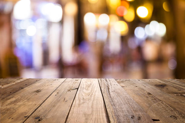 empty wooden table with defocused street lights at background - low lighting stock photos and pictures